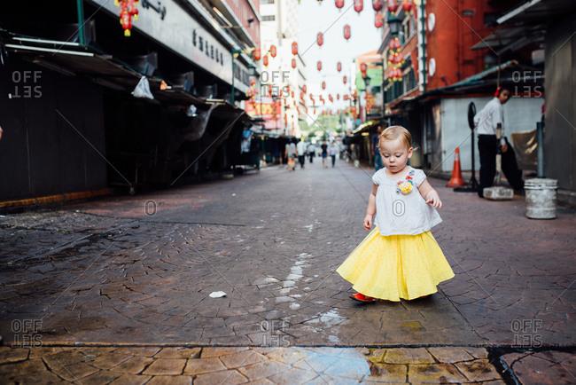 Toddler girl walking on a city street