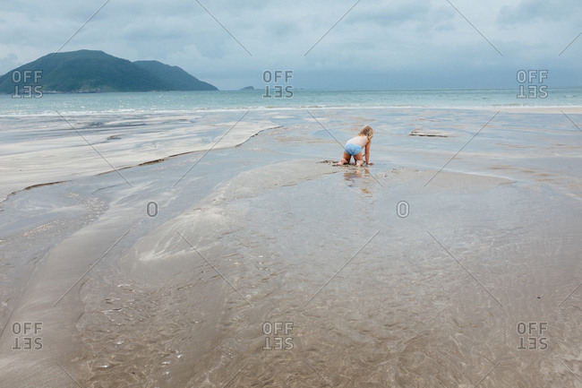 Girl playing in the sand at the seashore