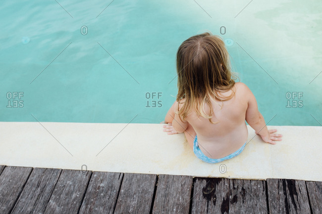 Girl sitting at the edge of a swimming pool