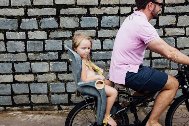 Girl riding in the back of her father's bike