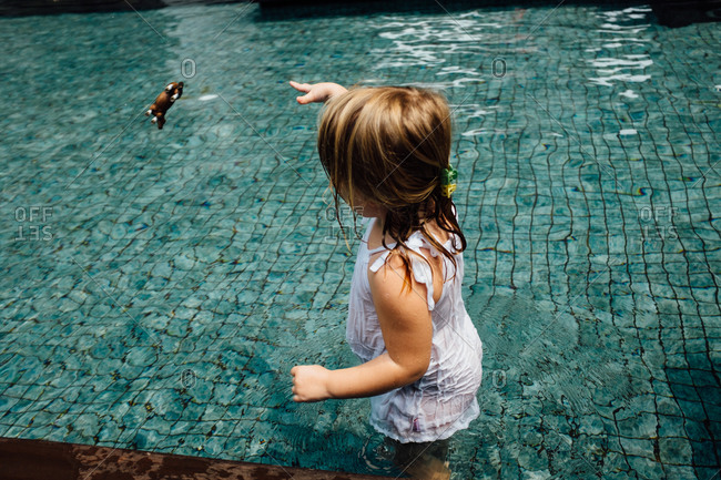 Girl playing with a toy in a swimming pool