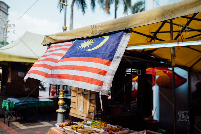 Malaysian flag hanging above a market stand