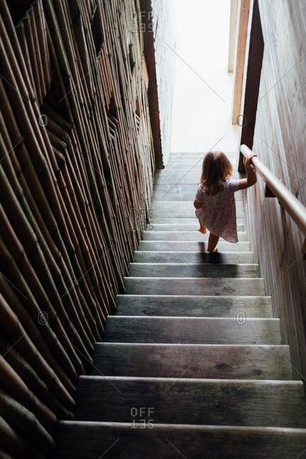 Girl holding railing while going down stairs