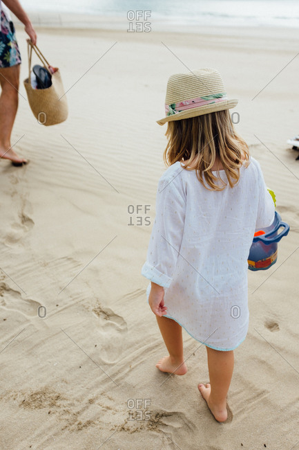 Girl carrying her toys onto the beach