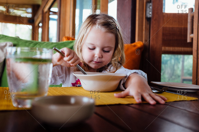 Girl eating food from a bowl