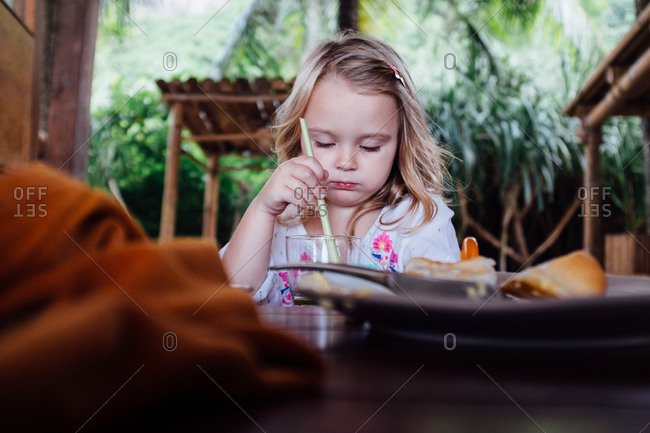 Girl at a table with a beverage and straw