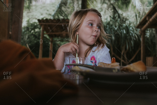 Girl at a table with a drink and straw