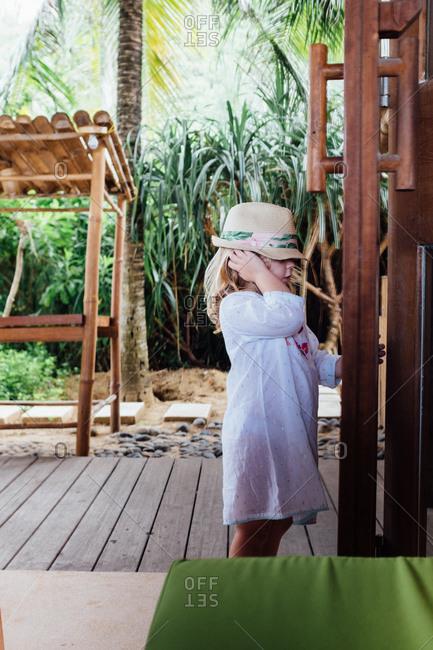 Girl wearing a hat opening a door