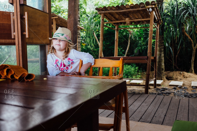 Girl at a table in a tropical cafe