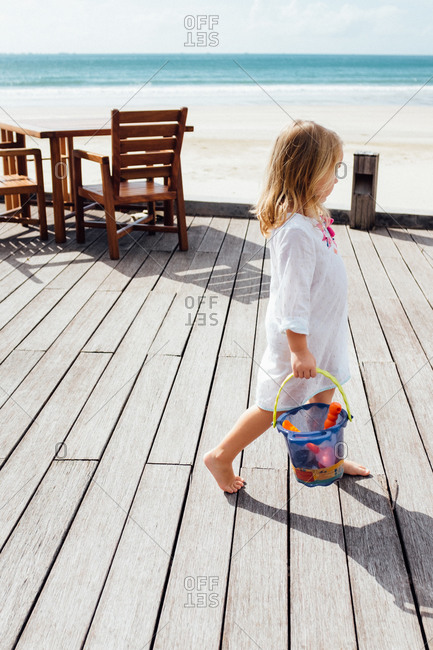 Girl with her toys on a beachfront patio