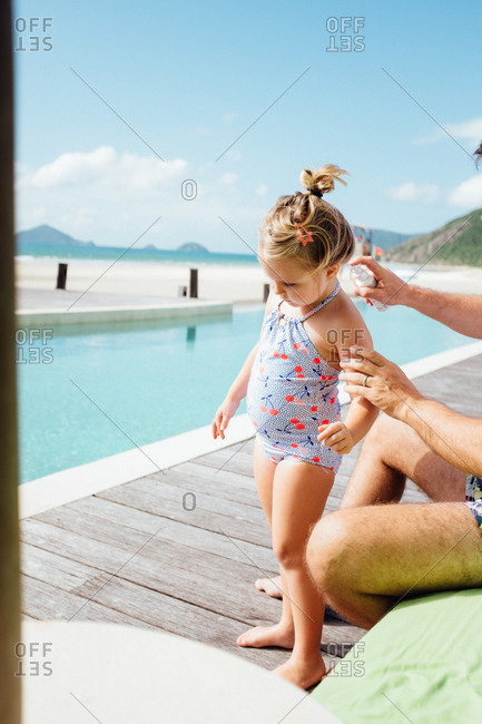 Father spraying sunblock on his daughter