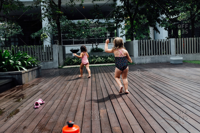 Little girls running on a swimming pool deck
