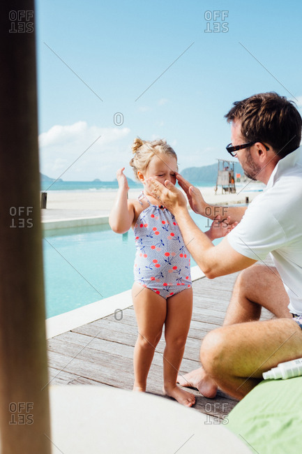 Father applying sunblock to his daughter's face