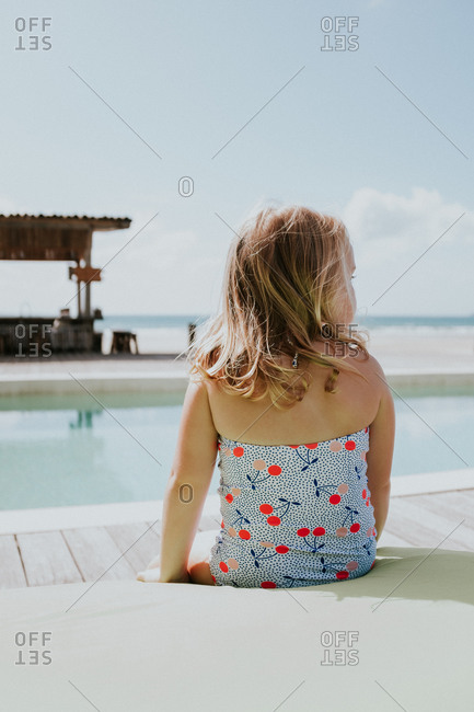 Girl sitting at the edge of a beachfront pool