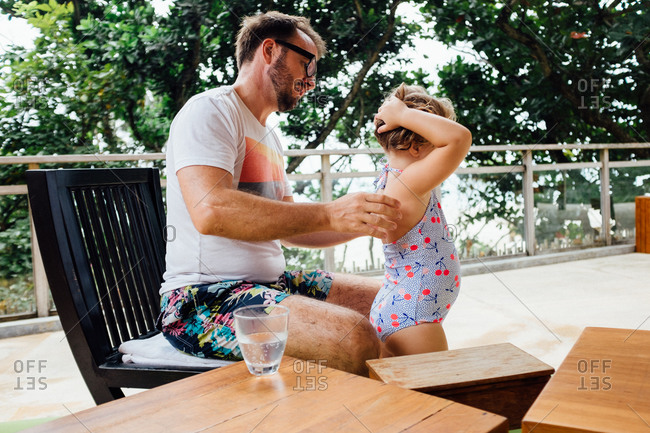 Father fixing his daughter's swimsuit