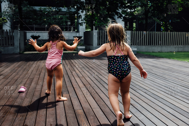 Girls chasing bubbles on a swimming pool deck