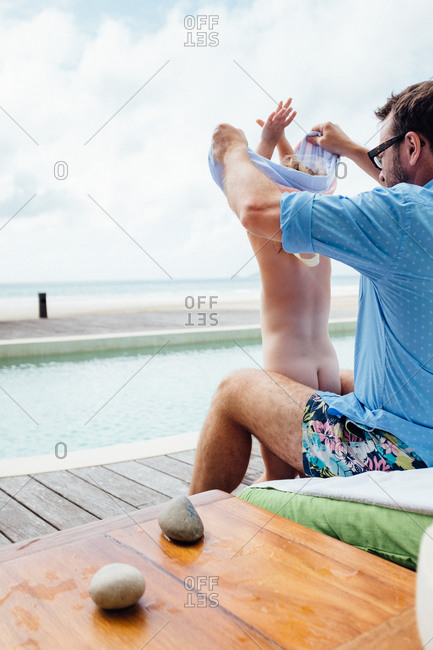Father dressing his daughter at a swimming pool