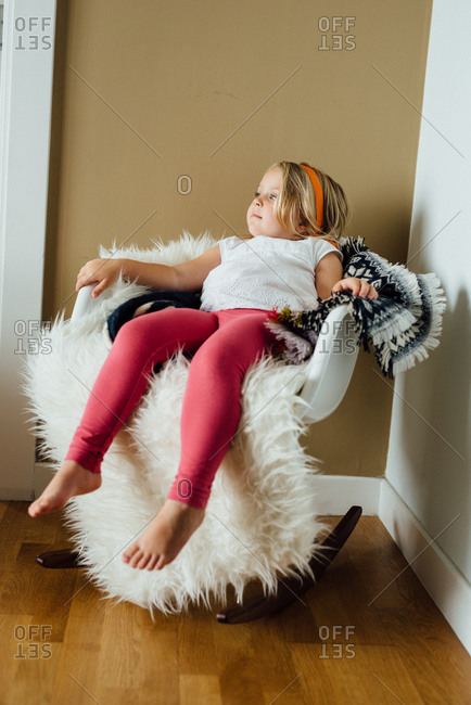Girl sitting in a rocking chair with blankets