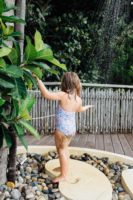 Girl rinsing mud off under an outdoor shower