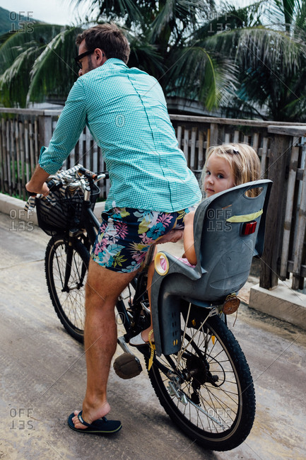 Girl riding on the back of her dad's bike