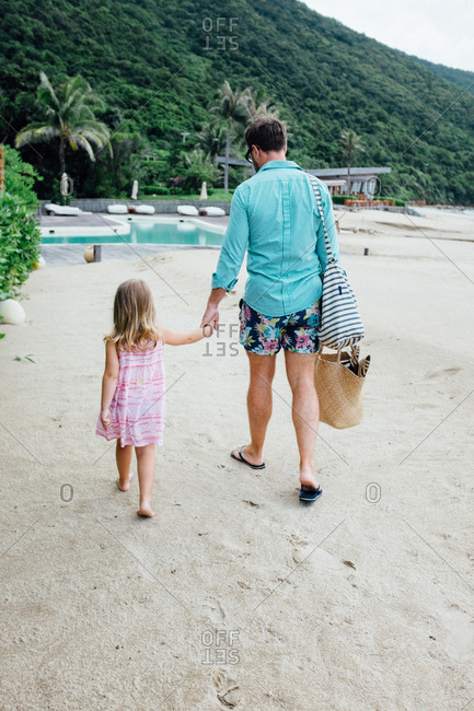 Father and daughter walking toward a resort pool