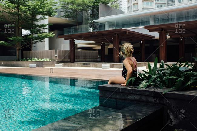 Girl sitting at a luxury modern hotel pool