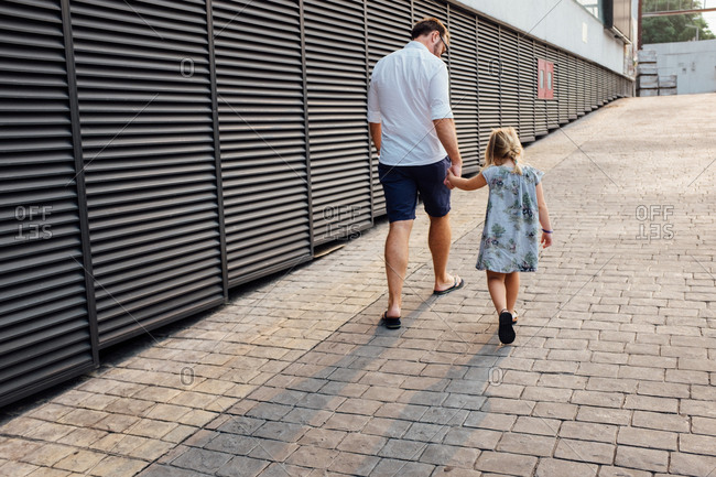 Father and daughter walking in an urban setting