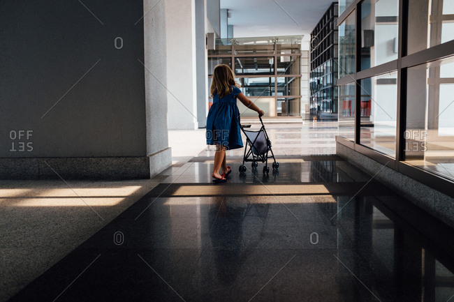 Girl pushing a doll carriage at a modern building