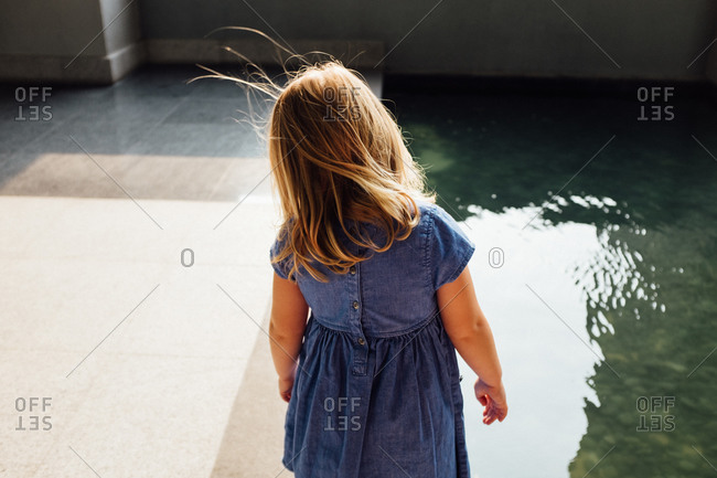 Girl looking at reflections in a swimming pool