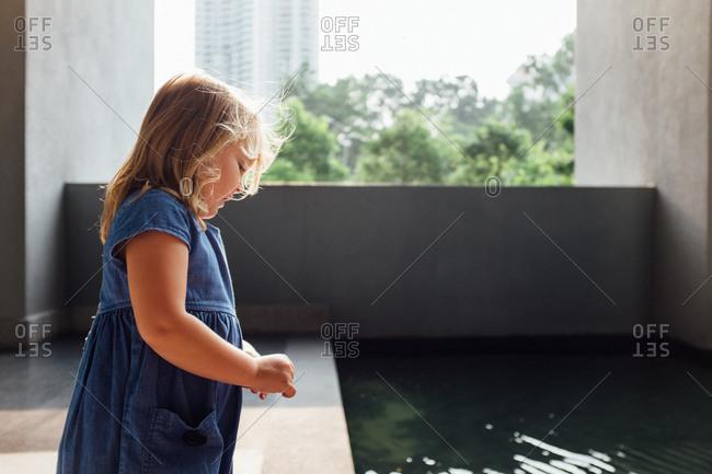 Girl looking at an urban modern swimming pool