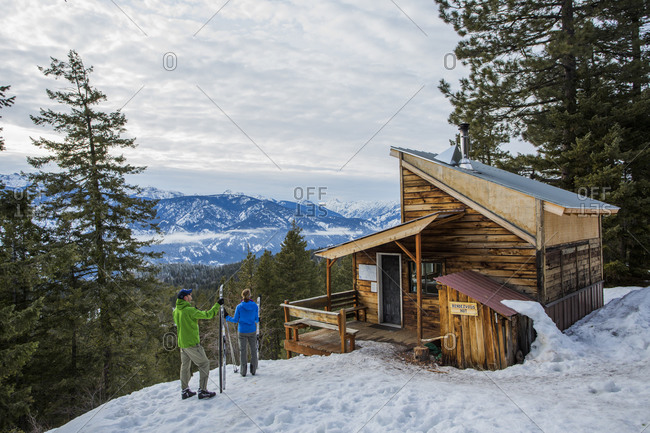 Washington, United States - January 31, 2015: Skiers standing beside the Rendezvous Cabin overlooking a mountain valley