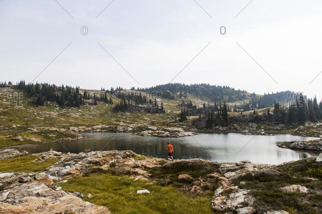 Young man walking near a mountain lake