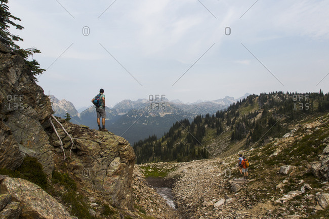 Man standing on a mountain overlooking  the valley below