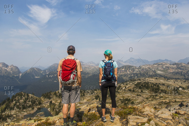 Man and woman standing on a mountain overlooking the valley below