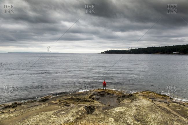 Man standing on the edge of an island overlooking water