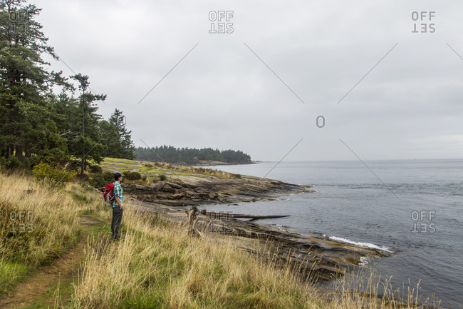 Galiano Island, Canada - September 17, 2015: Man standing on a grassy hill overlooking water