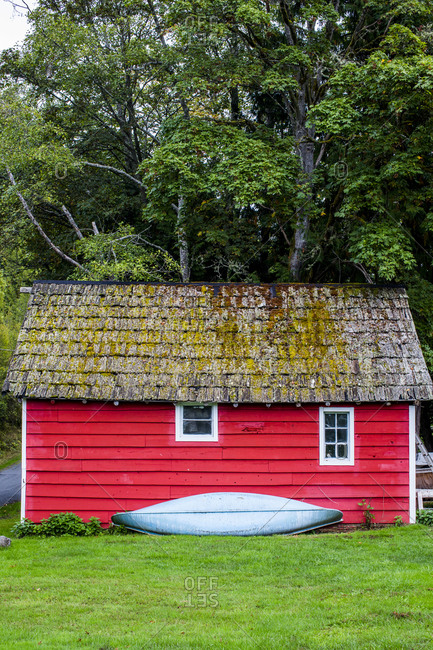 Red barn with a canoe resting against it