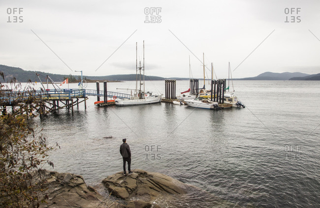 Man standing on rocks in a harbor on a cloudy day