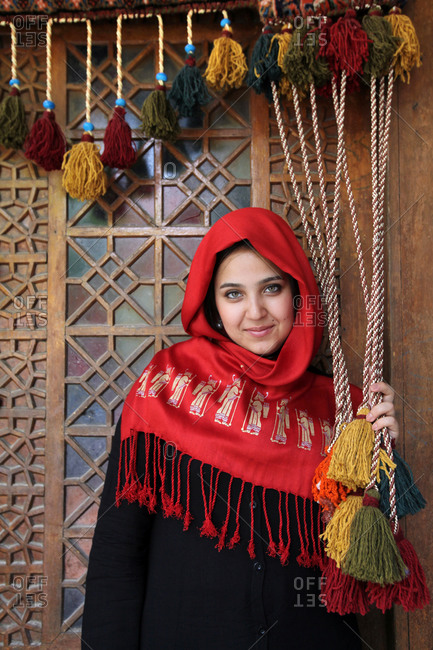 Portrait of a woman in red headscarf standing with tassels in doorway