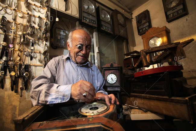 Clock and watch repairman working in his shop