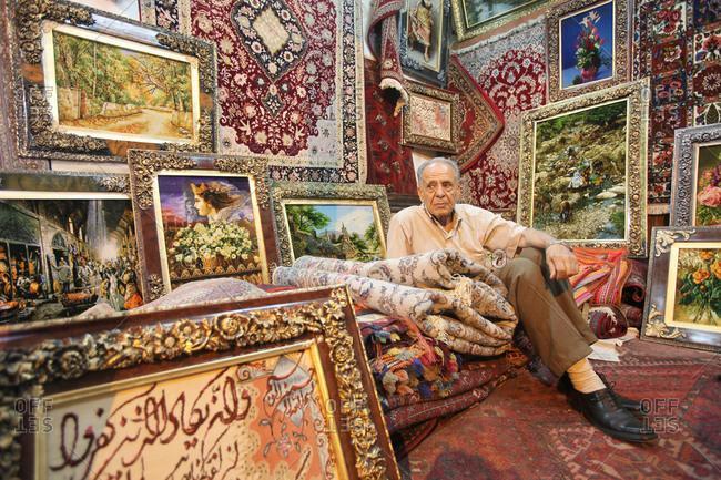 Shiraz, Iran - May 17, 2012: Salesman sitting on rugs in his home furnishing stall
