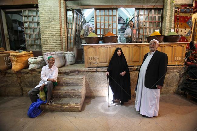 Shiraz, Iran - May 17, 2012: Muslim men and women at an outdoor market
