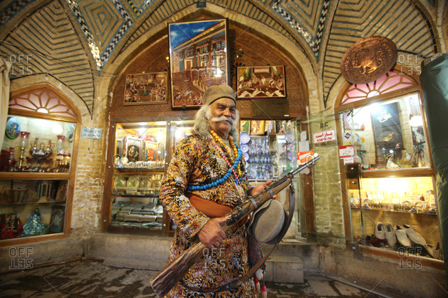 Shiraz, Iran - May 18, 2012: Smiling man with rifle in traditional costume in Iranian market