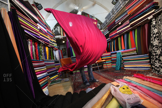 Person unrolling bolt of fabric in Iranian market stall