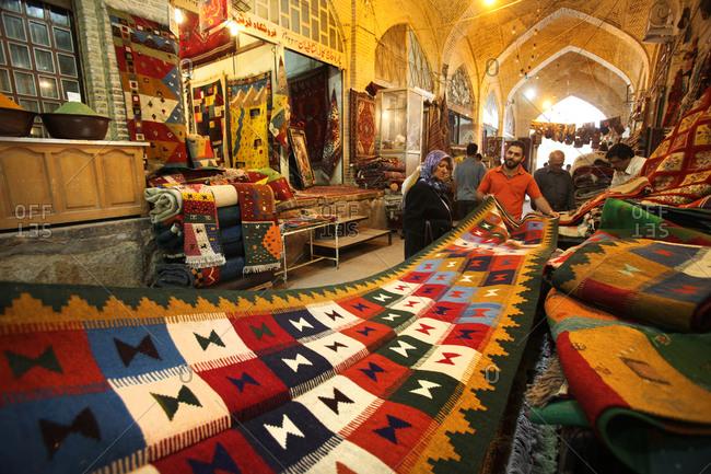 Shiraz, Iran - May 18, 2012: Carpet seller shows woman a rug in Iranian market