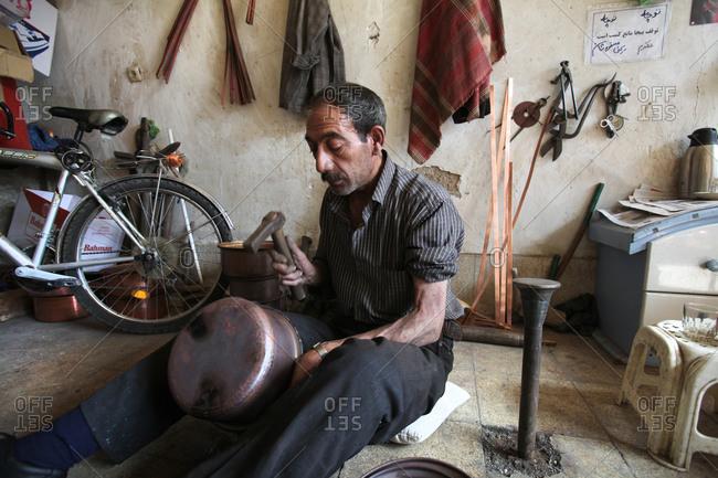 Zanjan, Iran - August 26, 2012: Man sitting on floor hammering a metal pot