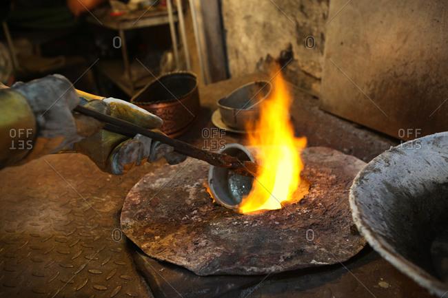 Man heating metal pot over furnace flame
