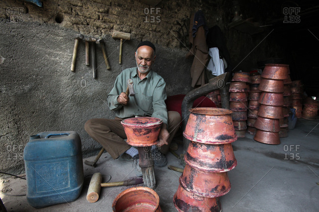 Man crafting copper rice pots in Iranian market