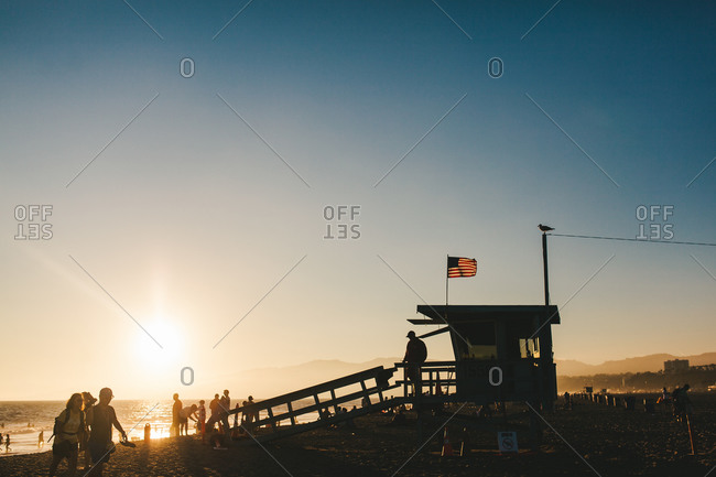 Santa Monica, LA - August 15, 2014: Lifeguard stand and beach goers at sunset