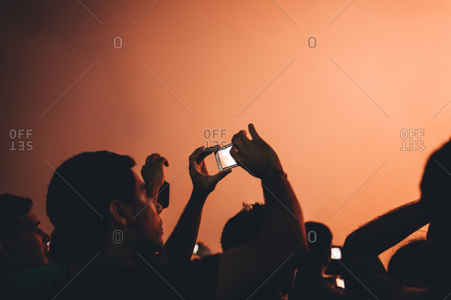 Singapore - December 31, 2013: Man in a crowd taking cellphone pictures